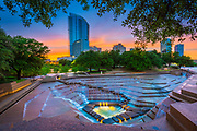 """The Fort Worth Water Gardens, built in 1974, is located on the south end of downtown Fort Worth between Houston and Commerce Streets next to the Fort Worth Convention Center. The 4.3 acre (1.7 hectare) Water Gardens were designed by noted New York architects Philip Johnson and John Burgee and were dedicated to the City of Fort Worth by the Amon G. Carter Foundation.<br /> The urban park is frequently billed as a """"cooling oasis in the concrete jungle"""" of downtown. Its focal points are three pools of water and a terraced knoll, which helps to shield the park from adjacent Interstate 30. The quiet meditation pool is encircled with trees and features a flat, still plane of water that cascades almost 90 degrees down to a sunken walkway. The aerating pool features multiple spray fountains. The main attraction of the Water Gardens is the active pool which has water cascading 38 feet (11 m) down terraces and steps into a small pool at the bottom. The park also contains over 500 species of plants and trees.<br /> The active pool was originally built for people to be able to walk down the terraced steps and experience the water tumbling around them. It was temporarily closed to the public after four people died there on June 16, 2004. Three children and one adult drowned after one of the children fell in the pool. The water was unusually deep due to a recirculating pump malfunction and heavy rains. The park was reopened on March 4, 2007 after being made safer by reducing the depth of the main pool from 9 ft (2.7 m) to 2 ft (0.61 m)."""