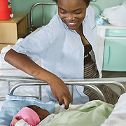 INDIVIDUAL(S) PHOTOGRAPHED: . LOCATION: St. Damien Hospital, Nos Petits Frères et Sœurs, Tabarre 41 Commune, Haïti. CAPTION: Fessiva Lamour,  a 20-year-old mother, looks towards her newborn daughter at St Damien Hospital.
