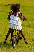 Kanak (Melanesian girls) on bicycle, Hnathalo, Lifou (island), Loyalty Islands, New Caledonia
