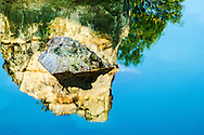 Painting-like image of a rock formation centered in the reflection of a cliff in a motionless lake, Tri Ton, An Giang Province, Vietnam, Southeast Asia