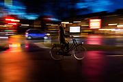 Een vrouw fietst 's avonds door Utrecht. De straten zijn nat van de regen.<br /> <br /> A young woman cycles in Utrecht on an evening. The streets are wet due to the rain.