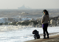 © Licensed to London News Pictures. 24/10/2011. Felixstowe, UK. A woman and a young boy watch the waves. Windy weather along Felixstowe promenade today 24th October 2011. Parts of the UK are braced for wet and windy weather over the next 24hrs . Photo: Stephen Simpson/LNP