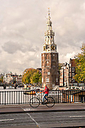Bicyclist crossing Prins Hendrikkade at the Montelbaanstoren Tower in Amsterdam.