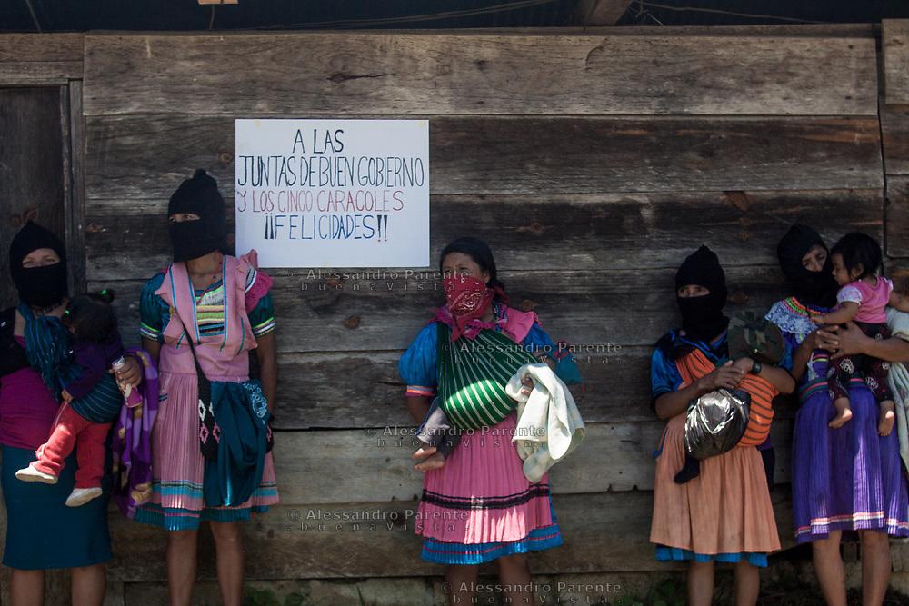 Gruppo di zapatiste si riparano all'ombra. Sullo sfondo un cartello felicita la giunta di buon governo che compiono 13 anni