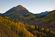 Dawn begins to light Gothic Peak with the entire spectrum of autumn colored aspens filling the valley beneath.