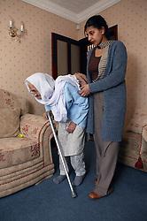 Granddaughter helping her Sikh elderly grandmother to walk,