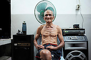 Kelabit sedentary Dayaks, living in longhouses, rely on fishing, hunting and farming to survive. Elderly man siting near music system. Limbang, Sarawak, Malaysia 2015<br /><br />Borneo native peoples and their rainforest habitat revisited two decades later: 1989/1991 and 2012/2014/2015. <br /> <br /> Sarawak's primary rainforests have been systematically logged over decades, threatening the sustainable lifestyle of its indigenous peoples who relied on nomadic hunter-gathering and rotational slash & burn cultivation of small areas of forest to survive. Now only a few areas of pristine rainforest remain; for the Dayaks and Penan this spells disaster, a rapidly disappearing way of life, forced re-settlement, many becoming wage-slaves. Large and medium size tree trunks have been sawn down and dragged out by bulldozers, leaving destruction in their midst, and for the most part a primary rainforest ecosystem beyond repair. Nowadays palm oil plantations and hydro-electric dam projects cover hundreds of thousands of hectares of what was the world's oldest rainforest ecosystem which had some of the highest rates of flora and fauna endemism, species found there and nowhere else on Earth, and this deforestation has done irreparable ecological damage to that region