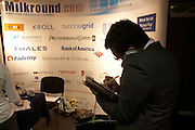 Taking notes on a stand at a graduate expo fair where company job recruiters meet young people starting work