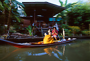 Buddhist Monks travel along the Damnoen Saduak canal in Thailand, performing blessings and receiving food.