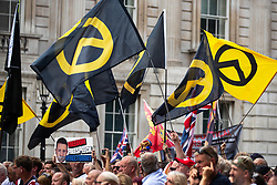 "© Licensed to London News Pictures. 14/07/2018. London, UK. Generation Identity flags are waved . Supporters of EDL founder Tommy Robinson ( real name Stephen Yaxley-Lennon ) and US President Donald Trump hold a "" Welcome Trump "" rally on Whitehall . Trump is currently in Scotland and Robinson is in HMP Hull . Photo credit: Joel Goodman/LNP"