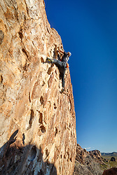 Climber climbing large cliff face, Hueco Tanks State Park & Historic Site, El Paso, Texas. USA.