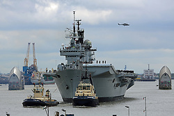 © Licensed to London News Pictures. 08/05/2013. London, UK. HMS Illustrious coming through the Thames Barrier this morning en route to Greenwich. She is in London as part of the Royal Navy's celebrations to mark the 70th anniversary of the Battle of the Atlantic. This is her last visit to London before being decommissioned.. Photo credit : Rob Powell/LNP