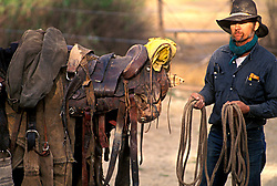 man in a cowboy hat prepaing ropes and saddles