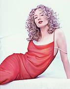 Actor Maria Patillo wearing a red chiffon strap dress, lounges on her hip on a quilted bed.  Room appears to be all white as she seem to pop out from the background.