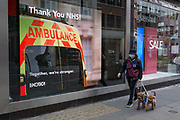 With the Coronavirus pandemic lockdown rules being eased, many businesses are slowly re-opening and the streets are filling up after months of a deserted city. A Londoner walks his dogs past a digital ad with a message of support and thanks for NHS key workers, on Long Acre in Covent Garden in the capitals West End, on 6th July 2020, in London, England.