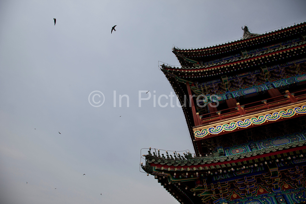 """Swifts fly above at Qianmen (literally """"Front Gate"""") is a gate in Beijing's historic city wall. The gate is situated to the south of Tiananmen Square and once guarded the southern entry into the Inner City. Although much of Beijing's city walls were demolished, Qianmen remains an important geographical marker of the city. The city's central north-south axis passes through Zhengyangmen's main gate. It was formerly named Lizhengmen meaning """"beautiful portal"""". Zhengyangmen was first built in 1419 during the Ming Dynasty and once consisted of the gatehouse proper and an archery tower."""