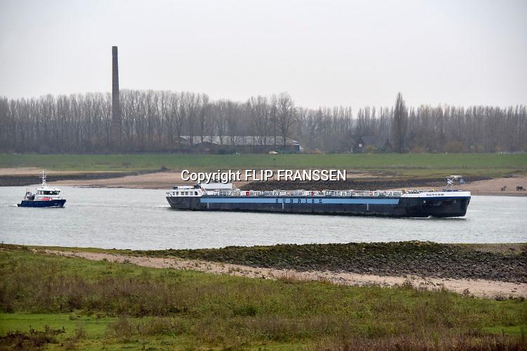 Nederland, the netherlands, Gendt, 29-11-2018Nog nooit stond het water in de Waal zo laag . Binnenvaartschepen varen langs de oever en de ooijpolder. Door de aanhoudende droogte staat het water in de rijn, ijssel en waal extreem laag . Laagterecord en de laagste officiele stand ooit bij Lobith gemeten. Schepen moeten minder lading innemen om niet te diep te komen . Hierdoor is het drukker in de smallere vaargeul . Door te weinig regenval in het stroomgebied van de rijn is het de waterafvoer extreem weinig . De Waal is het Nederlandse deel van de Rijn en de belangrijkste vaarroute van en naar Rotterdam en Duitsland . Aftakkingen zijn de minder bevaren Neder Rijn en IJssel. De levering, aanvoer van vracht, lading,grondstoffen, voor fabrieken en brandstof wordt problematisch. een politieboot vaart achter een tanker.Foto: Flip Franssen