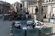 Diners and drinkers sit within street barriers where Fortnum & Mason have set up an outdoor restaurant and bar in front of the Royal Exchange at Bank, in the City of London, during the Coronavirus pandemic, on 9th September 2020, in London, England.