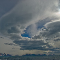 Wind-generated lenticular clouds hover over the South Atlantic Ocean and the Salveson Range of southeastern South Georgia, Antarctica.