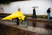 Men stand, walk with umbrellas and ride past on bicycles wearing large ponchos on a rainy street in San Cristobal de las Casas, Chiapas state, Mexico on June 27, 2008.
