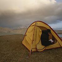 CHINA, Xinjiang Province. Mark Newcomb<br /> (MR) writes in his journal in camp by Lake Karakul in Pamir Mountains.