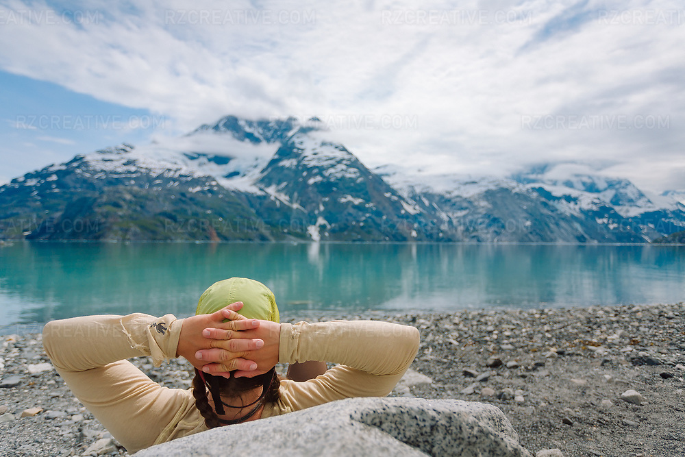 A woman relaxing on Topeka Beach in southeast Alaska's Glacier Bay National Park.