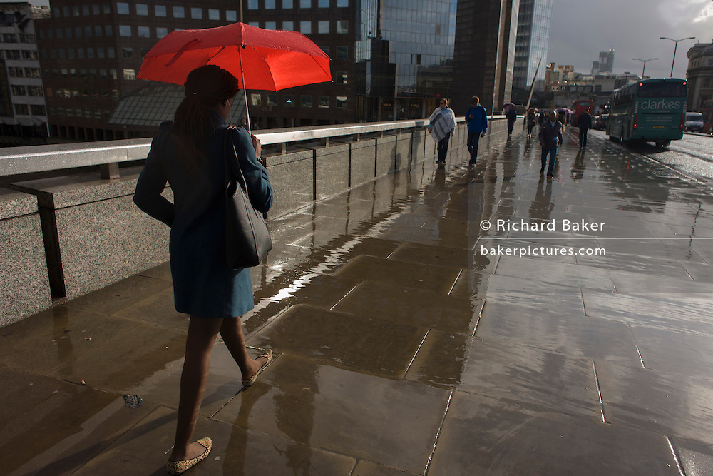 A woman carrying a red umbrella crosses London Bridge in the rain, southwards from the City to Southwark