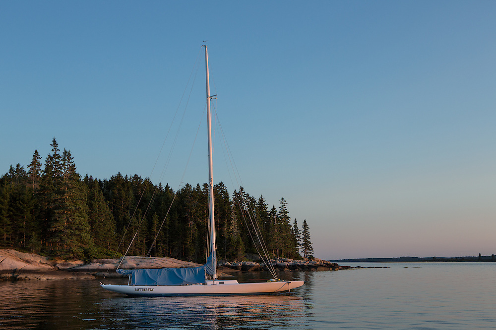 Center Harbor, Maine - 9 August 2014. Sloop Butterfly at anchor at sunset.
