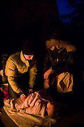 A young couple attends to their baby child by an evening fire at the Bluebell shelter in Chautauqua Park, Boulder, Colorado.