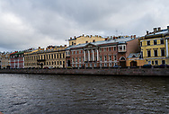 Colorful buildings line Griboedov Canal on an overcast summer day in St Petersburg.