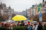 A group of tourists and their guide with a yellow umbrella at Wenceslas Square in the center of Prague.