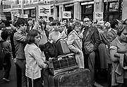 """Passengers waiting for a delayed train, Waterloo station, London. Despite being nationalised in 1947 """"as one of the 'commanding heights' of the economy"""", British Rail was not profitable for many years. Declining passenger numbers and financial losses in the late 1950s and early 1960s prompted the closure of many branch and main lines, and small stations, under the Beeching Axe. Coming and Going is a project commissioned by the Museum of London for photographer Barry Lewis in 1976 to document the transport system as it is used by passengers and commuters using public transport by trains, tubes and buses in London, UK."""