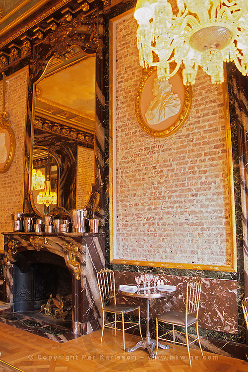 """Naked brick walls at The Baccarat Restaurant """"Le Cristal Room"""", in the old dining room. Crystal chandeliers and glasses. Designed by Philippe Starck. The Cristal Room restaurant: both gilded mirrors and naked brick walls"""