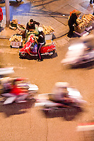 A young woman on a motorbike stops to purchase some bread as motorbikes continue to whizz by in the night.