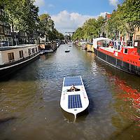 Nederland, Amsterdam , 14 september 2014<br /> Parade van Solar Boats en elektrische boten door de Amsterdamse grachten n.a.v. de 2e editie van de Amsterdam Solar Boat Parade, hét groene event van Amsterdam<br /> Solar boot parade door de grachten van Amsterdam zoals hier een verdwaalde solar boot die veel bekijks krijgt.<br /> Foto:Jean-Pierre Jans