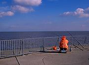 A728PC Man wearing orange jacket fishing from Gorleston pier Norfolk England