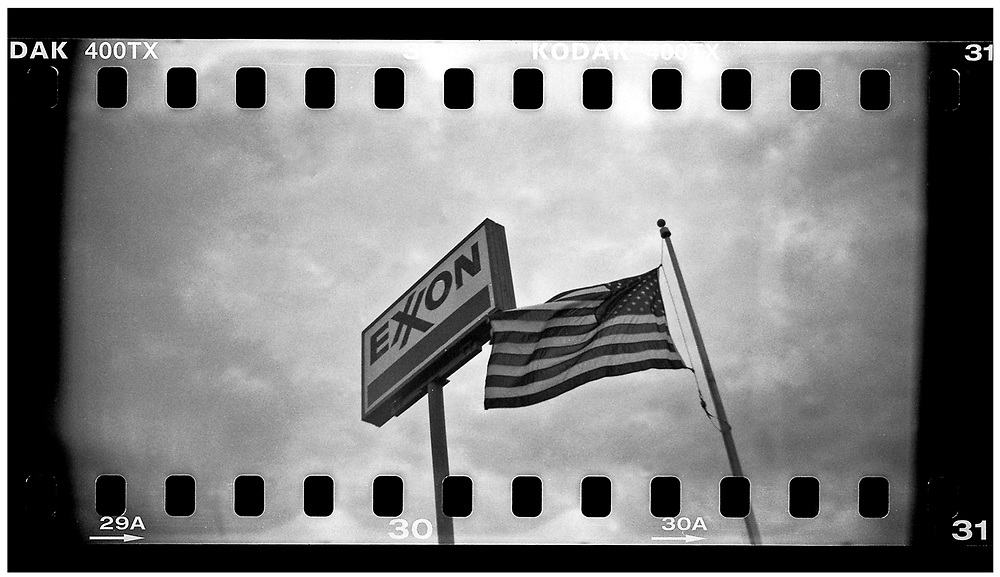 A U.S. flag blows in the wind at a gas station on the highway leading to Crawford, Texas, December 13, 2008. Bush moved to the small Texas town, population 705, in 1999 during his run for the presidency in 2000. The effect of the image was achieved by shooting 35mm black and white film in a medium format camera thereby exposing the entire negative including the sprocket holes of the film. REUTERS/Jim Young