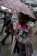 A Londoner walks along central London's Oxford Street during autumnal rain.