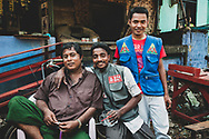 """Mawlamyine, Myanmar - October 24, 2011: Men in Mawlamyine, capital of Myanmar's Mon State.  It was in this city, formerly called Moulmein and currently Myanmar's fourth largest, that Eric Blair (a.k.a., George Orwell) briefly lived in the mid 1920s. It is the setting for one of his most famous essays, """"Shooting an Elephant."""" The essay begins with this line: """"In Moulmein, in Lower Burma, I was hated by large numbers of people – the only time in my life that I have been important enough for this to happen to me."""""""