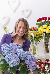 Portrait of mid adult woman in flower shop, smiling