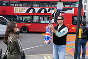 As a bus drives past arrying a billboard for the latest James Bond 'No Time To Die' starring Danial Craig, a visitor to the West End takes a picture of a woman, on 14th October, 2021, in Westminster, London, England.