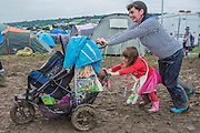 Arriving in the mud is a struggle for a mother and daughter with their buggy  - The 2016 Glastonbury Festival, Worthy Farm, Glastonbury.