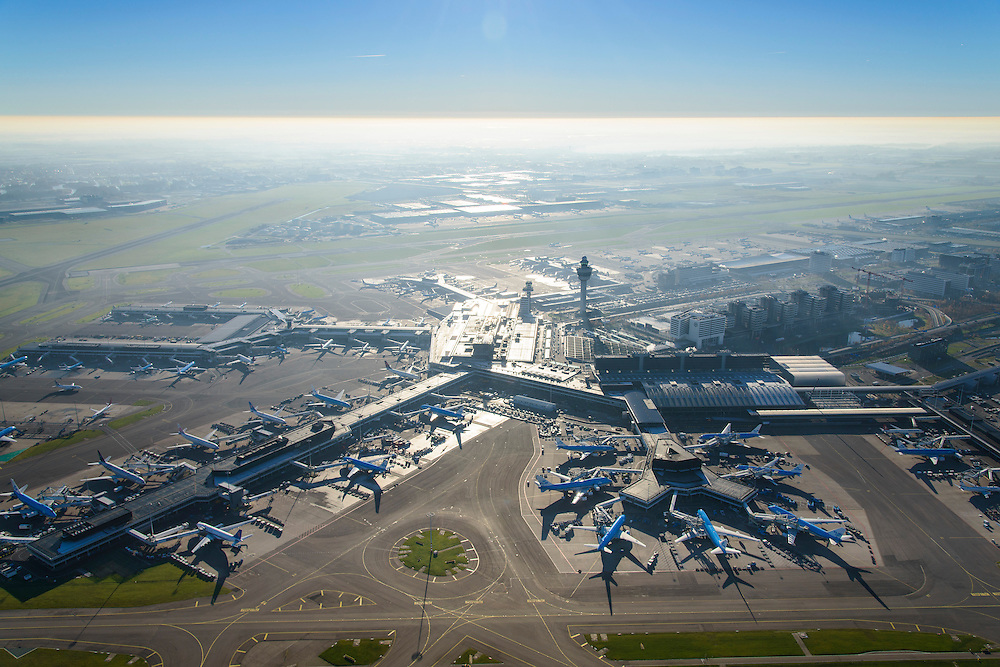Nederland, Noord-Holland, Haarlemmermeer, 11-12-2013; luchthaven Schiphol met tegenlicht. Stationsgebouw en verkeertoren met vluchtleiding omgeven door hotels en diverse kantoorgebouwen geexploiteerd door Schiphol vastgoed (Schiphol Real Estate). Aan de gates geparkeerde vliegtuigen van onder andere KLM.<br /> Schiphol Airport with backlight. Terminal building and control tower surrounded by hotels and office buildings operated by Schiphol Real Estate (SRE). At the gates of parked aircraft, amongst others KLM.<br /> luchtfoto (toeslag op standard tarieven);<br /> aerial photo (additional fee required);<br /> copyright foto/photo Siebe Swart