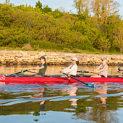 A morning rowing club (Portland Community Rowing Association) rows next to the Eastern Promenade in Portland, Maine. Casco Bay.