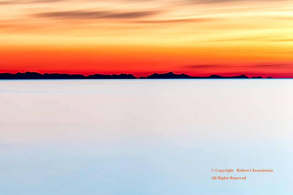 Orange-Red Jericho: A surrealistic orange-red sunset, with the distant coastal islands held in silhouette, from Jericho beach, Vancouver British Columbia Canada.