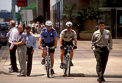 Stock photo of two bicycle policemen riding through an intersection in downtown