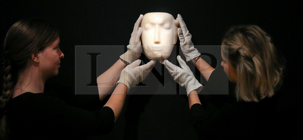 "© Licensed to London News Pictures. 12/11/2018. London, UK. Staff members holds ""The Man Behind the Mask"", a Henry Moore's masterpiece (British, 1898-1986). (Estimate: £1,000,000-1,500,000). The work is one of 12 known, small carvings by Moore titled Mask, and, uniquely, is the only one carved from alabaster.<br /> Bonhams Modern British and Irish Art photocall. Auction to be held on 14 November 2018. Photo credit: Dinendra Haria/LNP"