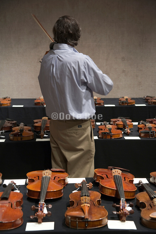 violins displayed at an auction for musical instruments