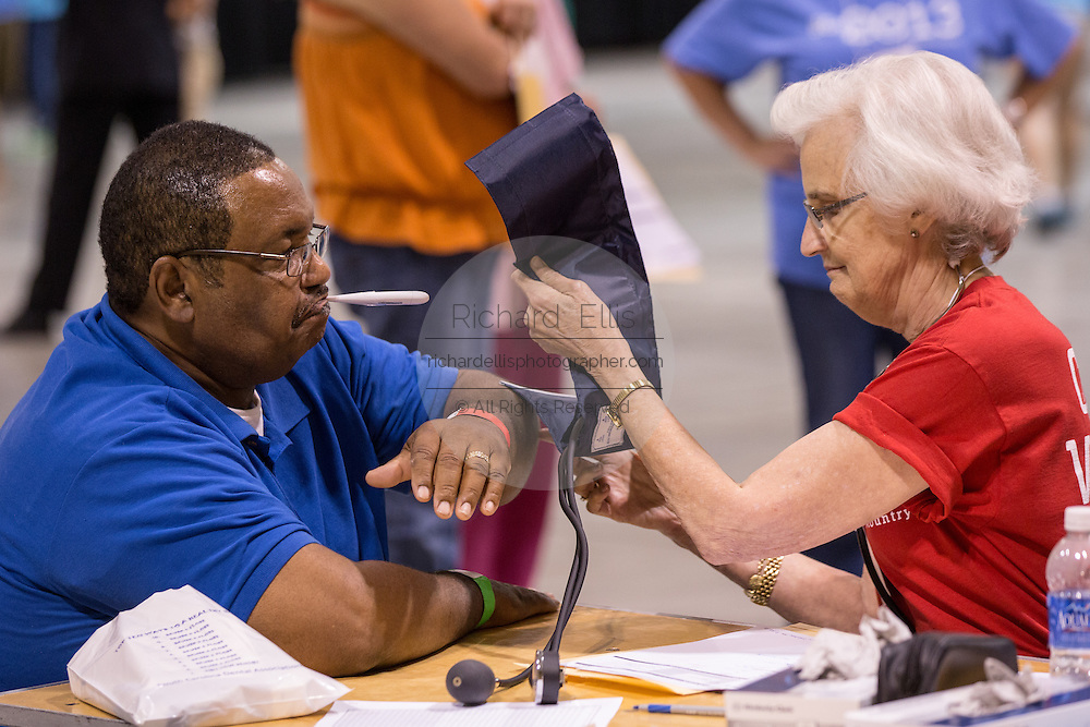 A volunteer nurse checks a mans blood pressure during a free medical mission held by the SC Dental Association on August 23, 2013 in North Charleston, South Carolina. More than 1,000 people showed up to receive free dental and medical care.