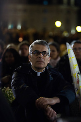 """A priest praying with candles on the place saint michel in front of a statue of Virgin Mary during an evening of prayer and songs organized by Catholics community the day after Notre Dame Cathedral blaze with a march organized from Saint-Sulpice church to Saint Michel and finally next to Notre Dame Cathedral in Paris early on April 16 the day after the beginning of the fire , 2019. A huge fire that devastated Notre-Dame Cathedral is """"under control"""", the Paris fire brigade said early on April 16 after firefighters spent hours battling the flames. Photo by Raphael Lafargue/ABACAPRESS.COM"""